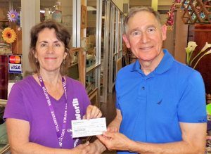 David Moss, chairman of the Mission Endowment Fund of PEACE Lutheran Church, presents a check for $500 from MEF to Women of Worth.