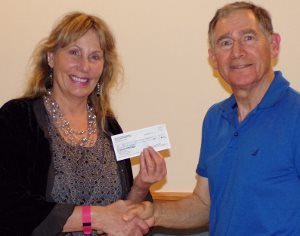 David Moss, financial secretary for PEACE Lutheran Church's Mission Endowment Fund, presents a donation from MEF to Donna Raibley, founder of One Source Empowering Caregivers.