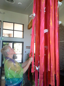 Peace Lutheran Church's liturgical artist, Ingrid Dreyer, arranges a floating sculpture in the church atrium in preparation for the festival of Pentecost, one of the three great holy days along with Easter and Christmas. The doves are a symbol of the Holy Spirit, and the red evokes flame, another Pentecost symbol.