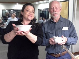 A woman and a man holding bowls, with people eating in the background.