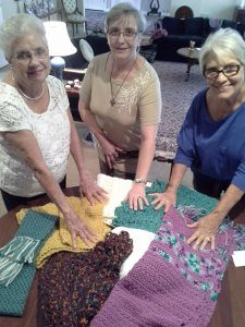Bobbi Meyer, Pastor Eileen Smith Le Van and Judy Kenney pray over shawls they have knitted and crocheted.