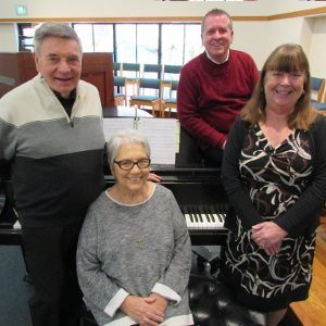 Two men and two women standing by a grand piano.
