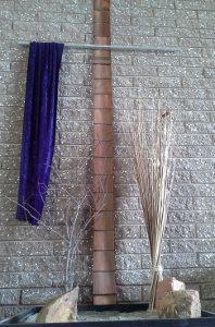 Stark scene of a cross draped with a purple cloth.