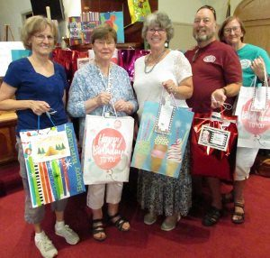 Interfaith Food Ministry Development Director Kate LaFerriere, center, accepts 45 birthday party bags from Rolling River Day Camp Director Margaret Boothby, second from right, during the camp's family program Thursday at Grass Valley United Methodist Church. Also pictured are IFM board member Cheri Eckholt, left, and, from right, Rita Kahil and IFM Vice-president Rick Kahil. Campers were asked to donate the items for their service project.