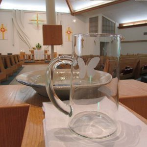 A glass pitcher in front of a ceramic baptismal font, with the church Sanctuary in the background.