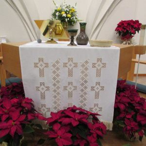 Altar with white cloth, Holy Communion vessels, and red poinsettias at the base.