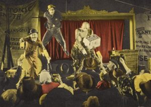 A stage, with a man dangling from a suspended bar. Two other men on the stage give bottles to the audience.