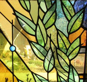 Stained glass window showing green leaves.