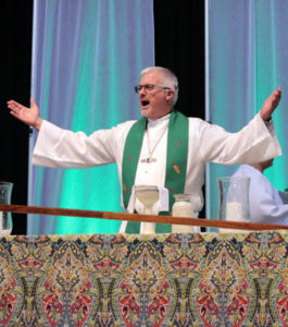 A white man with gray hair and glasses, wearing a long white robe and a green stole, with his arms outstretched.