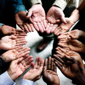 White, black and brown hands, palms up, close together in a circle.