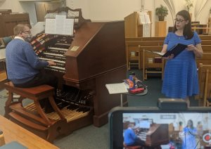 A white man wearing a blue sweater plays a song on an organ, while a white woman in a blue dress sings from sheet music.